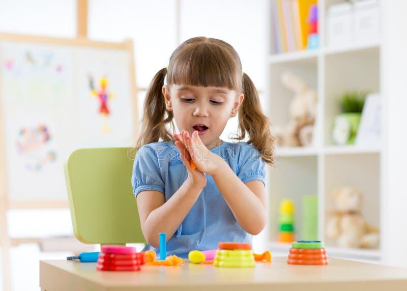 Gullig liten flicka som spelar med plasticine royaltyfria bilder