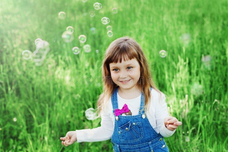 Gullig liten flicka som spelar med såpbubblor på den utomhus- gröna gräsmattan, lyckligt barndombegrepp, barn som har gyckel royaltyfri fotografi