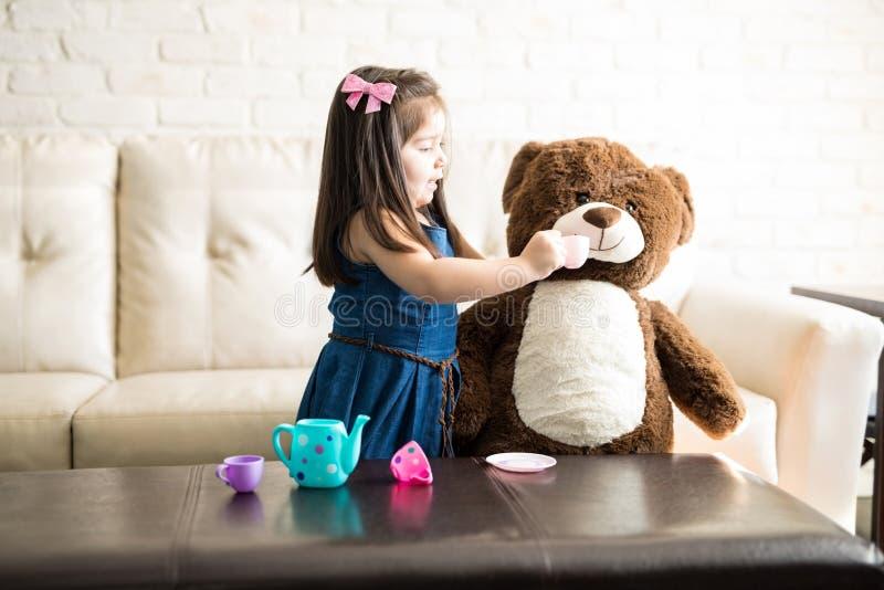 Gullig liten flicka som spelar tebjudningen med nallebjörnen royaltyfria bilder