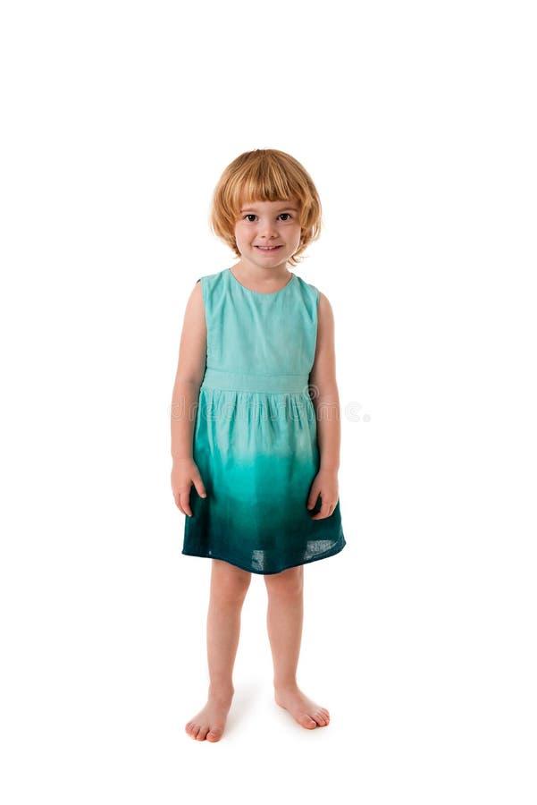 Gullig liten flicka som står barfota isolerad arkivfoto
