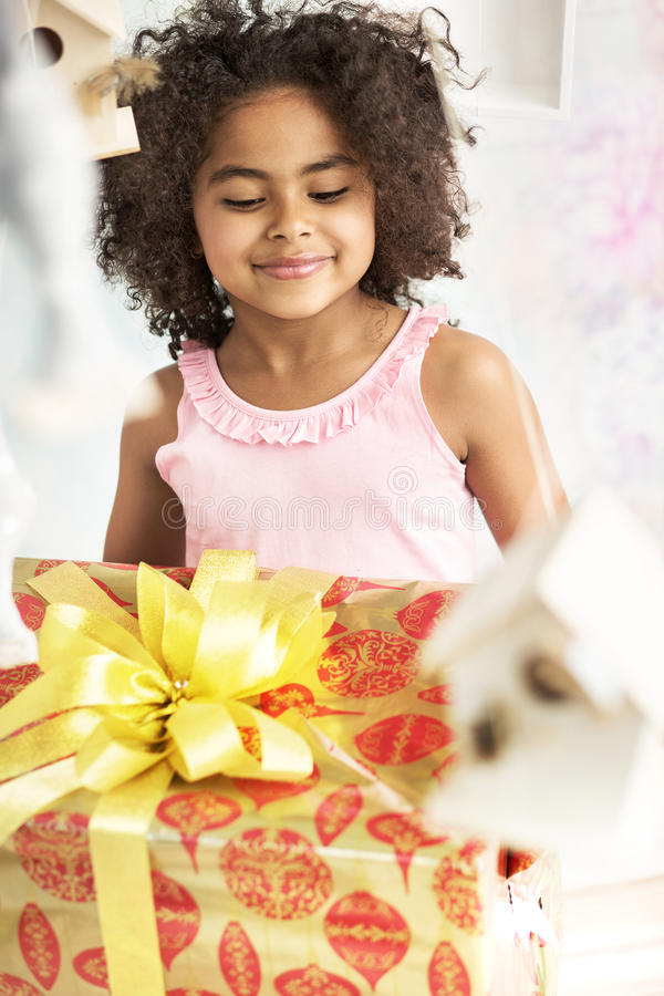 Gullig liten flicka som stirrar på födelsedaggåvan arkivfoton
