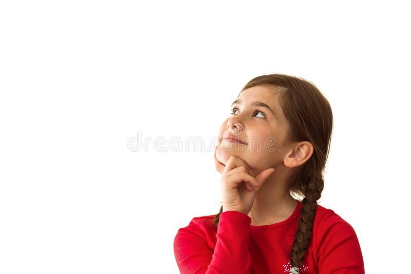 Gullig liten flicka som tänker och ser upp royaltyfri foto