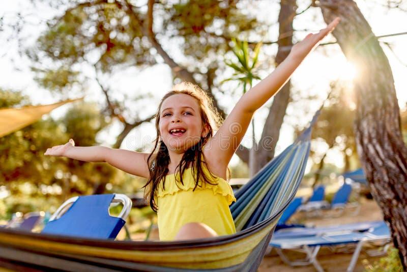 Gullig liten flicka som tycker om att ligga i hängmatta på stranden royaltyfri bild