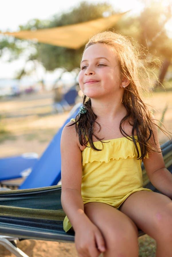 Gullig liten flicka som tycker om att ligga i hängmatta på stranden arkivbilder
