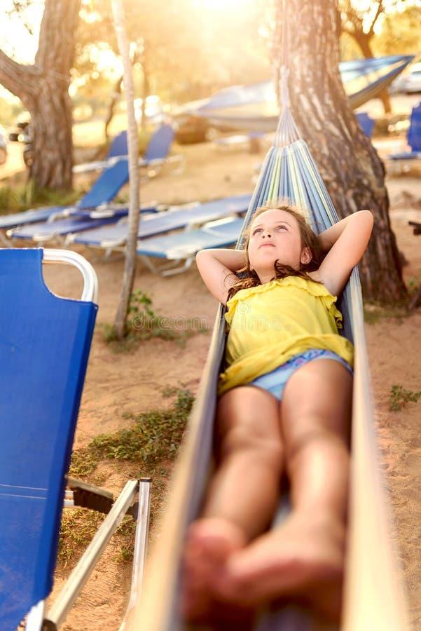 Gullig liten flicka som tycker om att ligga i hängmatta på stranden royaltyfria foton