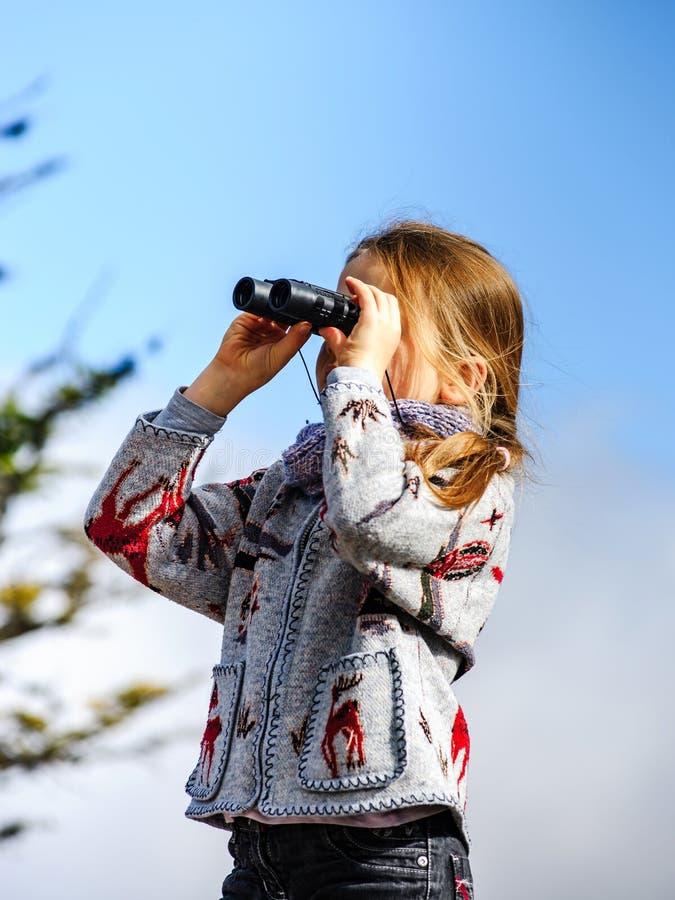 Gullig liten flicka som utforskar att använda för fjällängberg som är binokulärt T royaltyfria foton