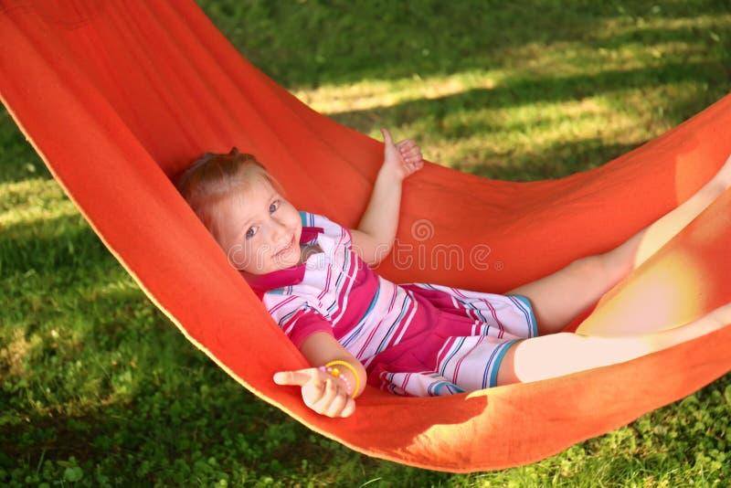 Gullig liten flicka som utomhus kopplar av i hängmatta på solig dag royaltyfria bilder