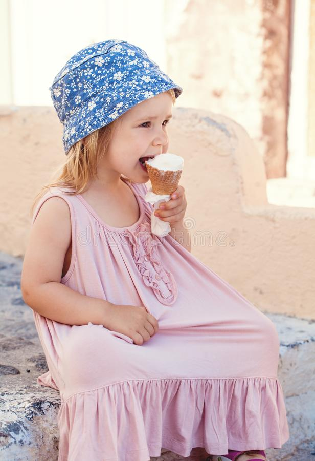 Gullig liten flicka som utomhus ?ter glass royaltyfria bilder