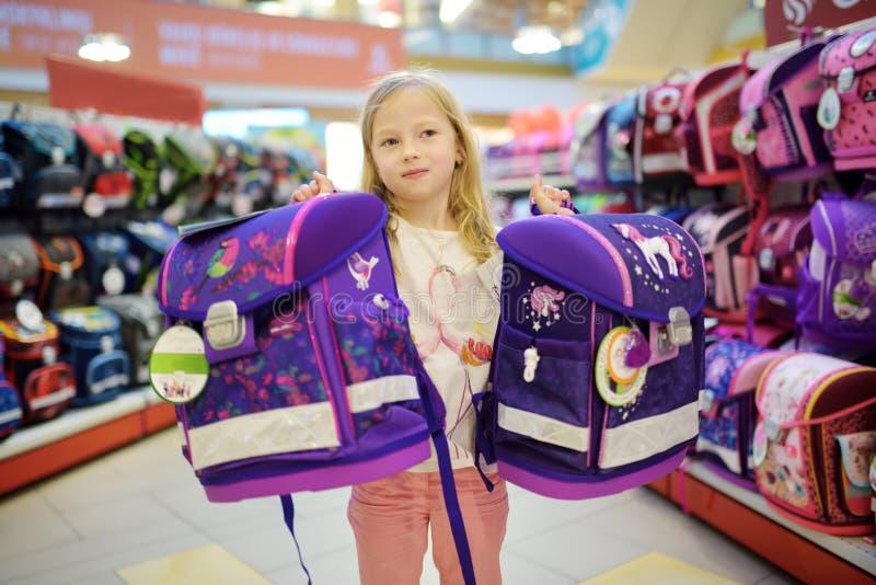 Gullig liten flicka som väljer en skolväska, innan att starta grupper Förtjusande ryggsäck för elevköpandeskola i ett lager royaltyfri foto