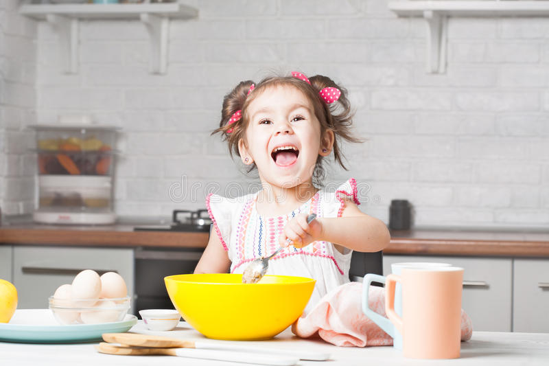 Gullig liten flickabagare på kök med stekheta ingredienser arkivbild