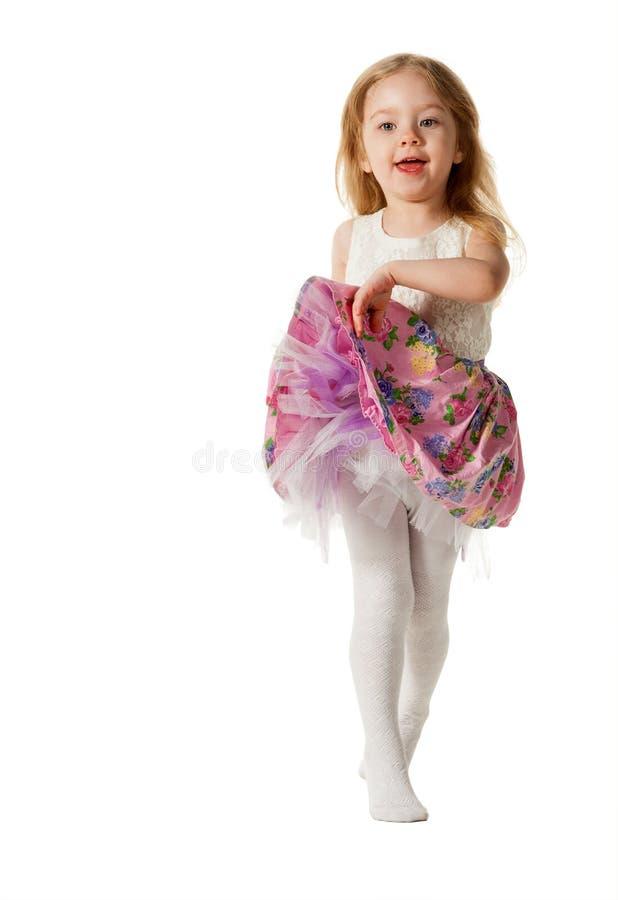 Gullig liten flickabanhoppning med glädje som isoleras på vit bakgrund royaltyfria foton
