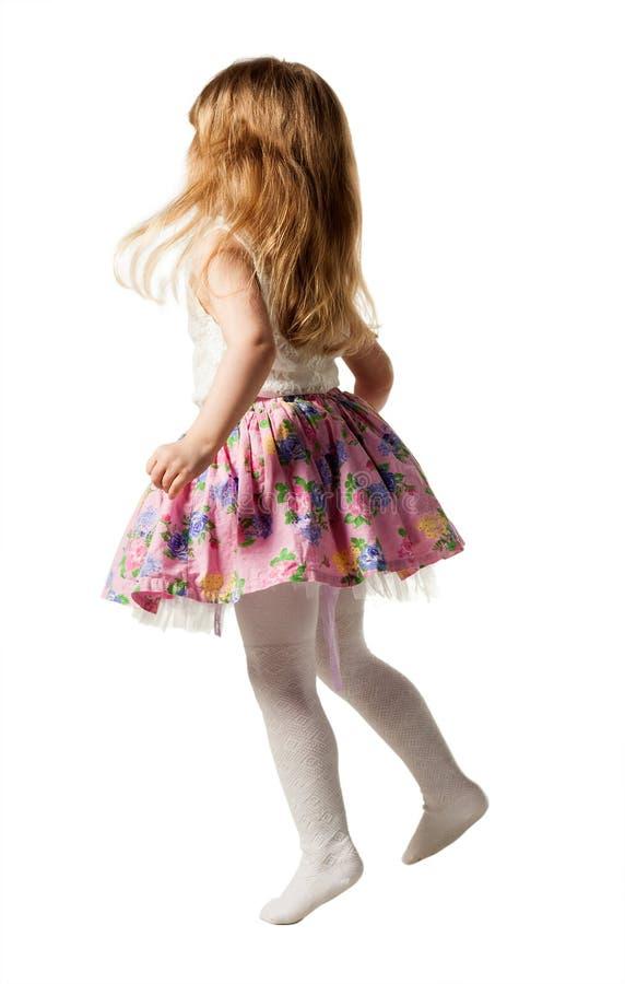 Gullig liten flickabanhoppning med glädje som isoleras på vit bakgrund royaltyfria bilder