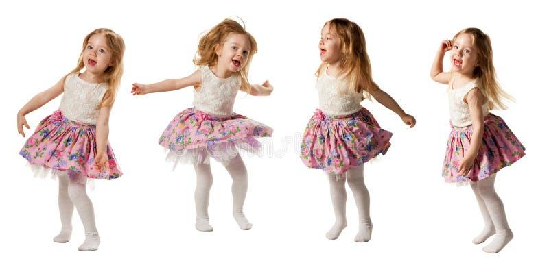 Gullig liten flickabanhoppning med glädje som isoleras på vit bakgrund arkivfoto