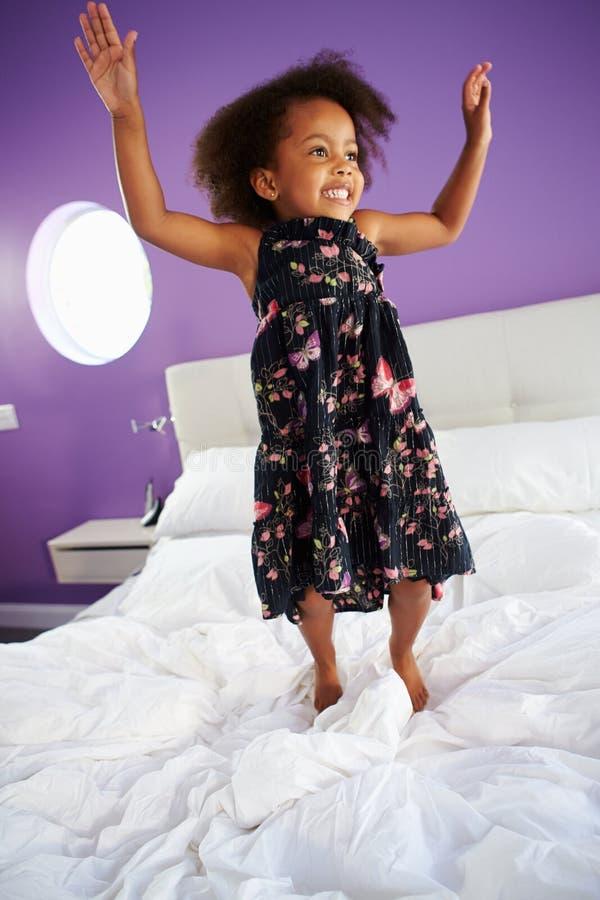 Gullig liten flickabanhoppning på förälders säng arkivbilder