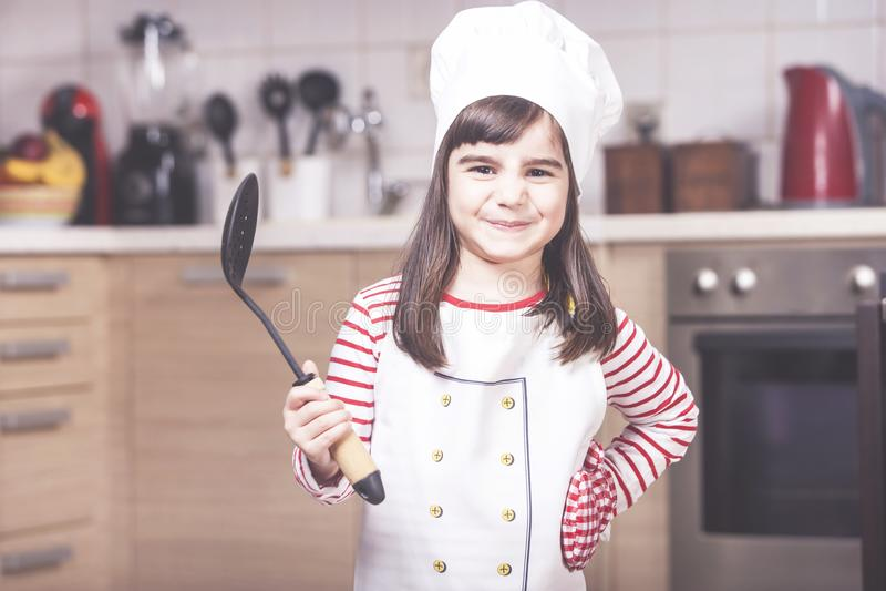 Gullig liten flickakock som poserar i köket arkivbild