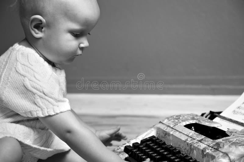 Gullig liten flickamaskinskrivningbokstav på tappningskrivmaskinstangentbordet royaltyfria bilder