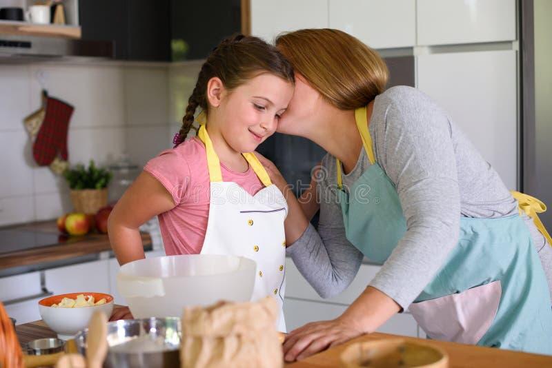 Gullig liten flickaportionmoder i köket arkivbild