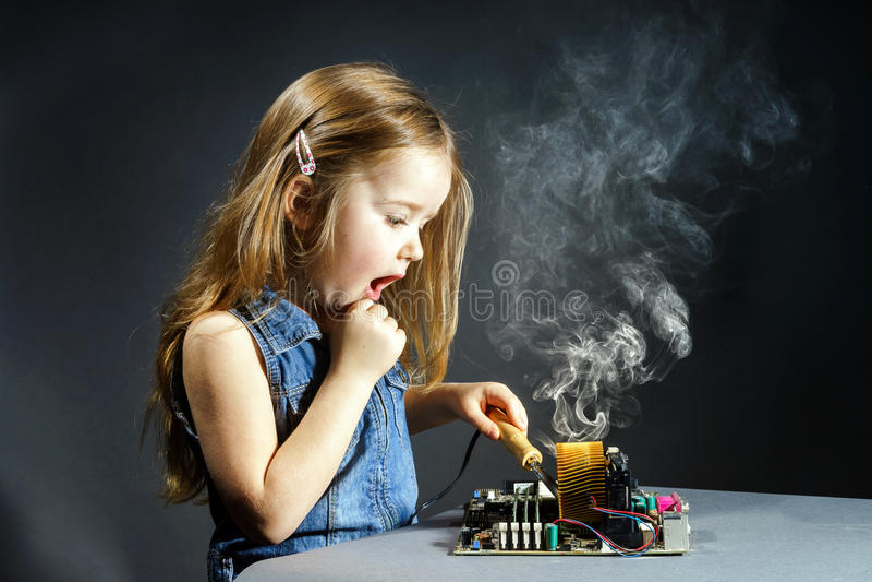 Gullig liten flickareparationselektronik vid tunnbindare-biten royaltyfria foton