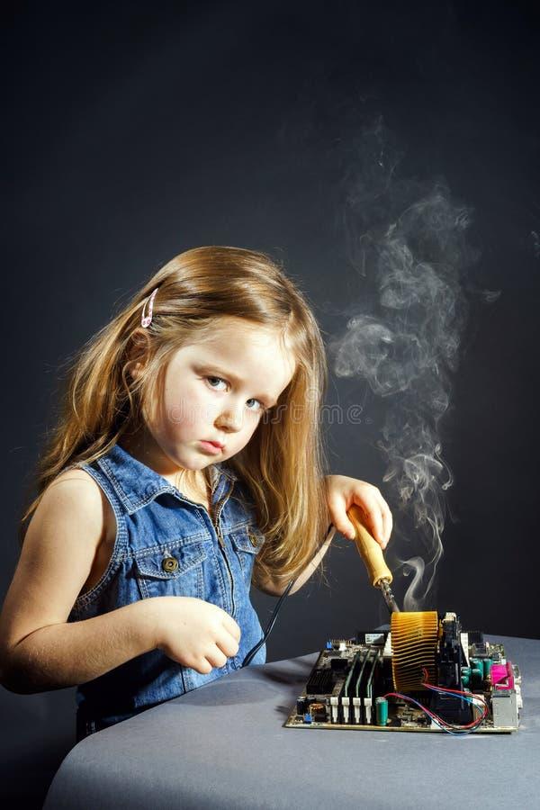 Gullig liten flickareparationselektronik vid tunnbindare-biten royaltyfria bilder