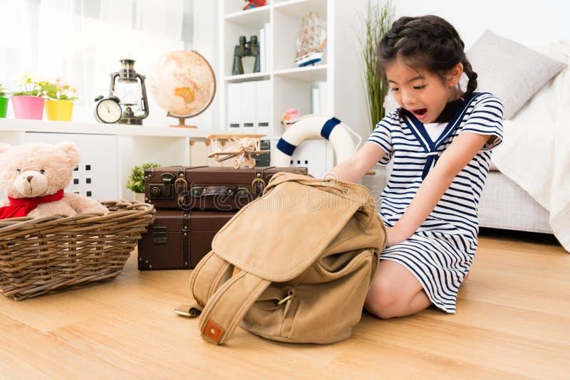 Gullig liten flickasjöman som öppnar den personliga ryggsäcken royaltyfria bilder