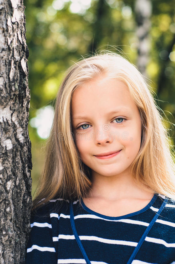 Gullig liten flickastående nära trädbjörk royaltyfri foto