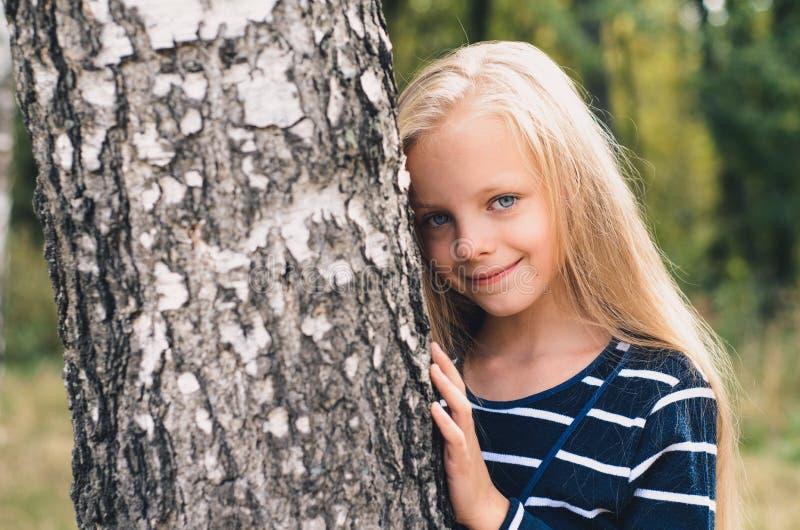 Gullig liten flickastående nära trädbjörk royaltyfria foton