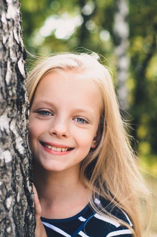 Gullig liten flickastående nära trädbjörk royaltyfria bilder