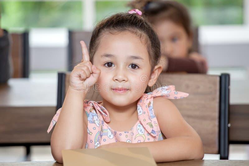 Gullig liten flickastudent som pekar fingret upp i klassrumskola Snilleunge stor id? klyftigt sammanträde för barn på skrivbordfö arkivbilder