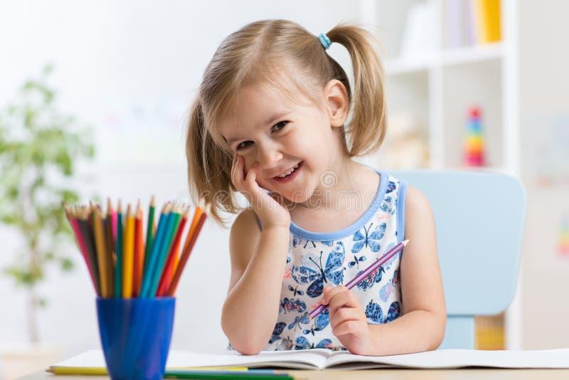 Gullig liten flickateckning med färgrika blyertspennor på papper Nätt barn som inomhus hemma målar, daycare eller dagis royaltyfri fotografi