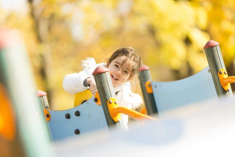 Gullig liten gilr som spelar på lekplatsen på hösten royaltyfria bilder
