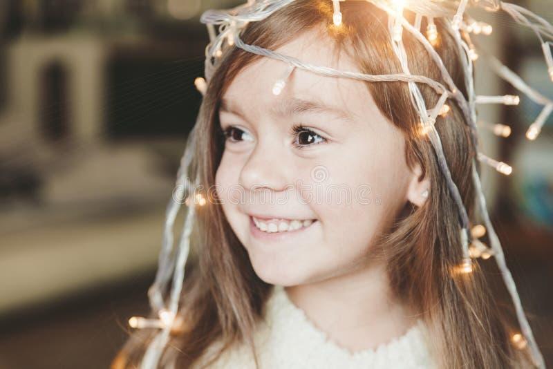 Gullig liten le flicka med den lysande girlanden för jul på hennes huvud arkivfoton