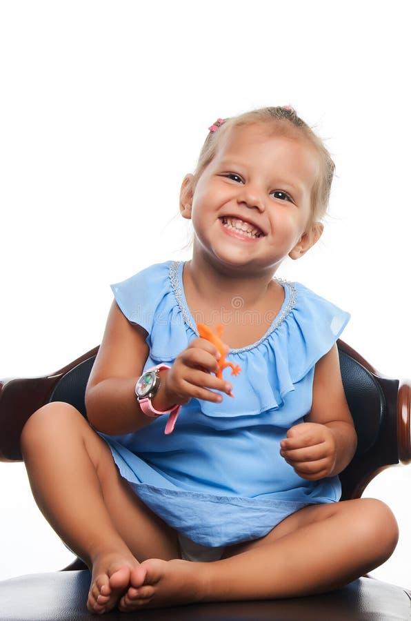 Gullig liten le flickastående över grå bakgrund royaltyfri fotografi