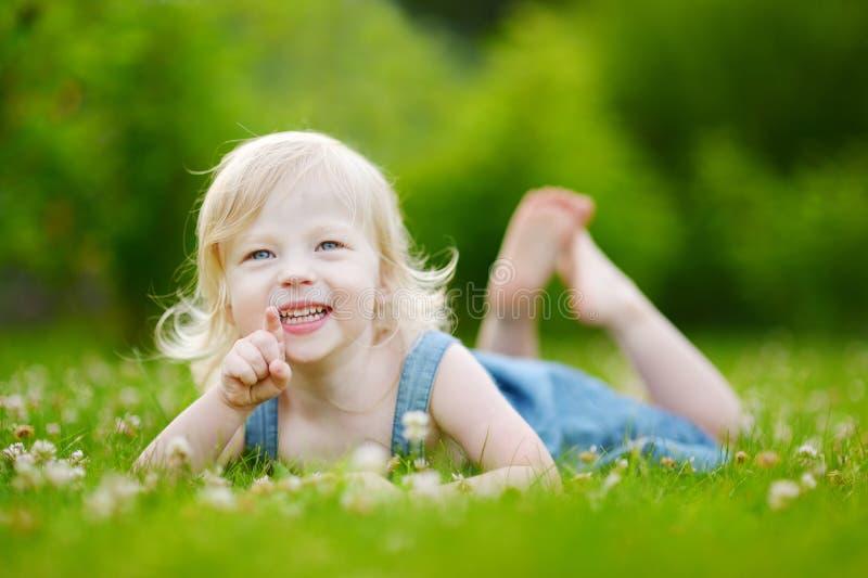 Gullig liten litet barnflicka som lägger i gräset royaltyfri foto