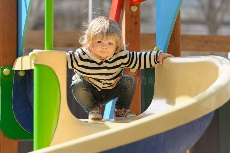 Gullig liten litet barnflicka som ner glider barnens glidbana royaltyfria bilder