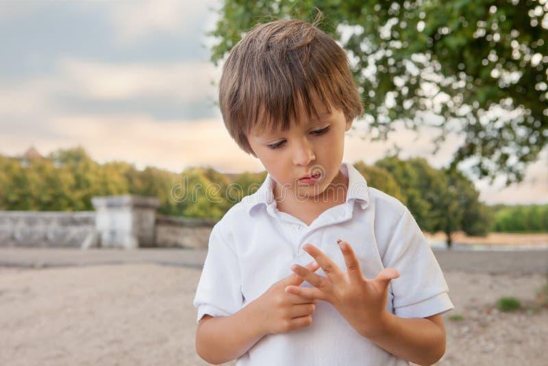 Gullig liten litet barnpojke som spelar med nyckelpigan som är utomhus- i PA arkivbilder