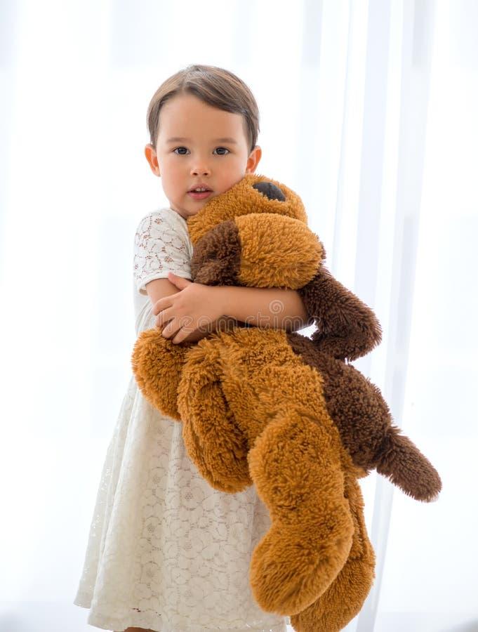 Gullig liten lycklig flicka som kramar den stora bruna nallebjörnen royaltyfri foto