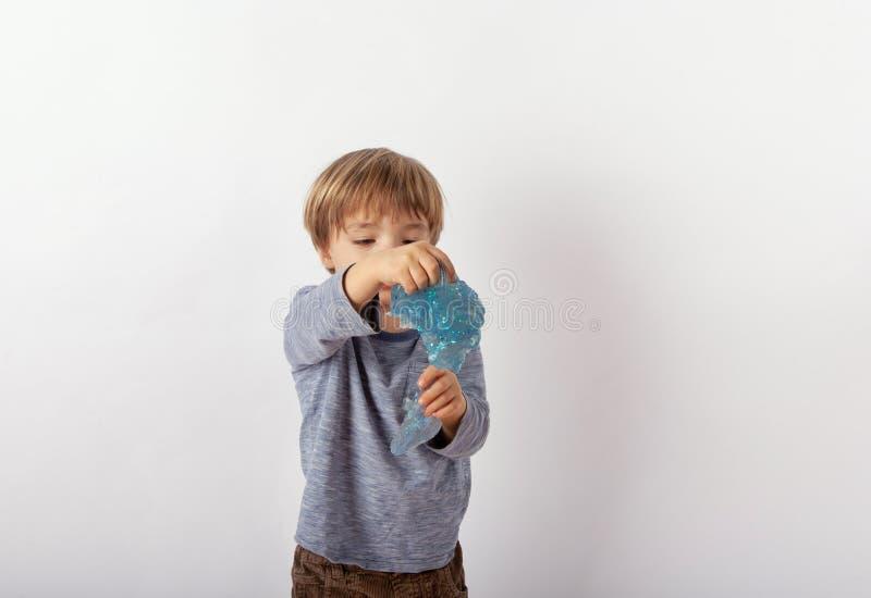 Gullig liten pojkeuppvisning blänker slam arkivfoton