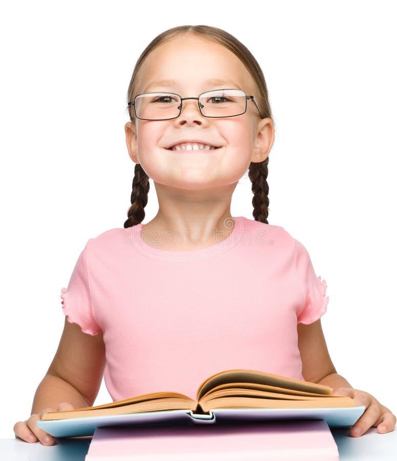 Gullig liten schoolgirl med en bok royaltyfri foto