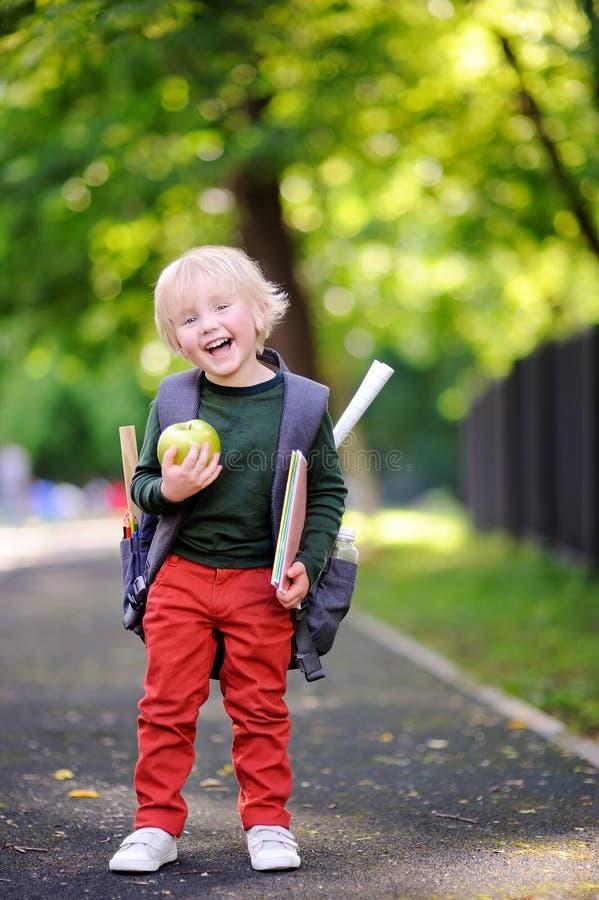 Gullig liten skolpojke utomhus på solig höstdag tillbaka begreppsskola till arkivfoton