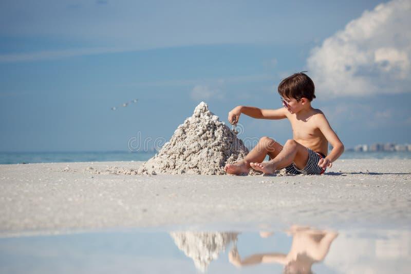Gullig liten sonbyggnadssandslott på stranden royaltyfria bilder