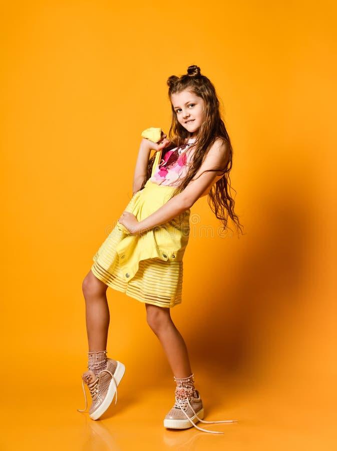 Gullig liten tonårig flicka i en stilfull kjol och omslagskläder som ser kameran och ler mot en gul studiovägg arkivfoto