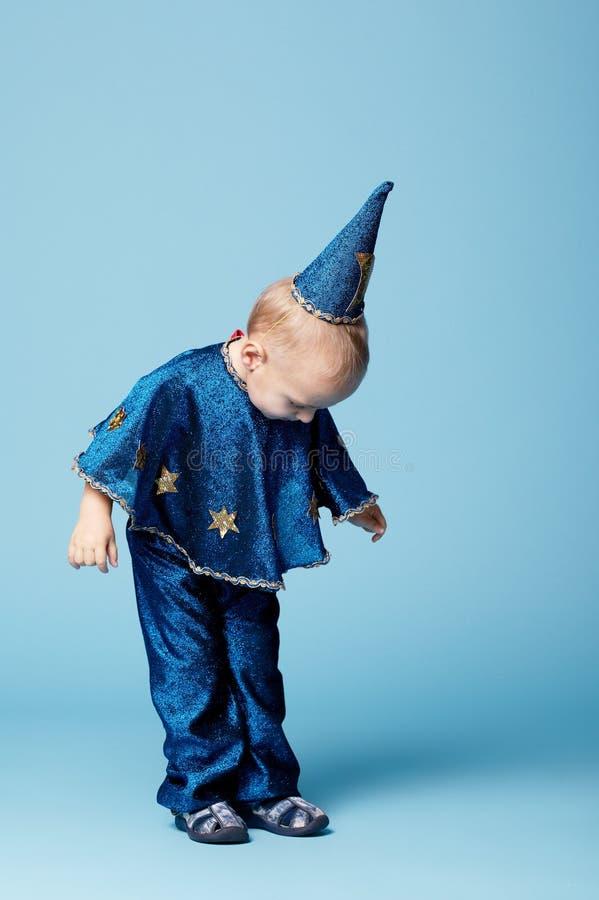Gullig liten trollkarlstående på blått royaltyfri fotografi