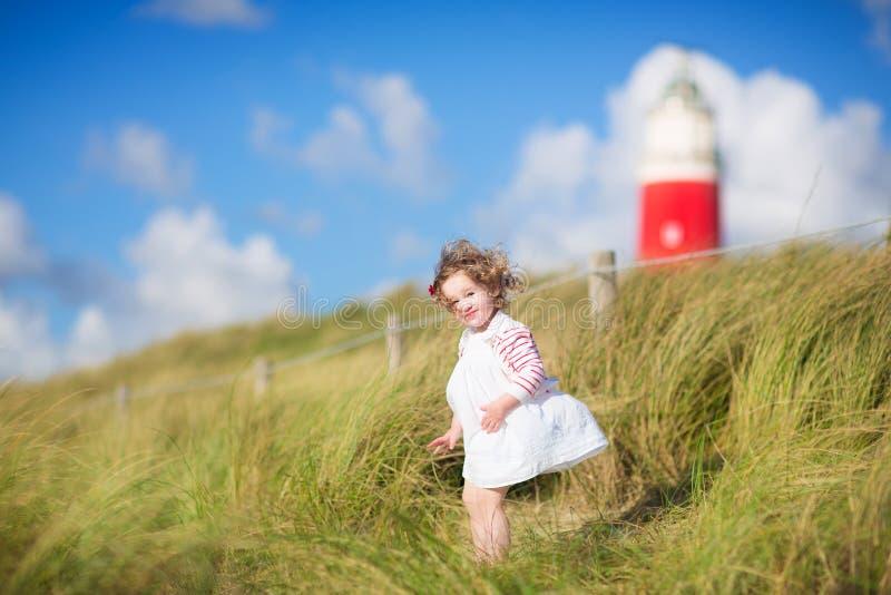 Gullig litet barnflicka bredvid en röd lightshouse på en strand arkivfoto