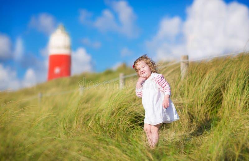 Gullig litet barnflicka bredvid röd lightshouse på stranden arkivbilder
