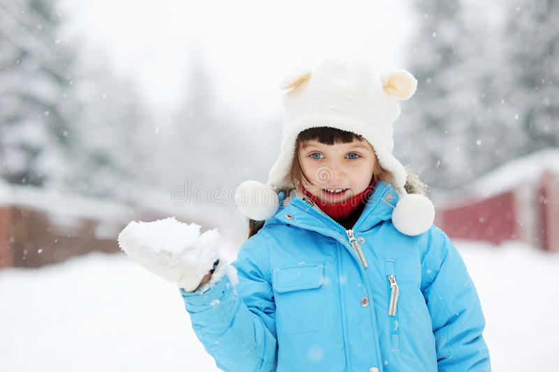 Gullig litet barnflicka i snowsuit som utomhus poserar fotografering för bildbyråer