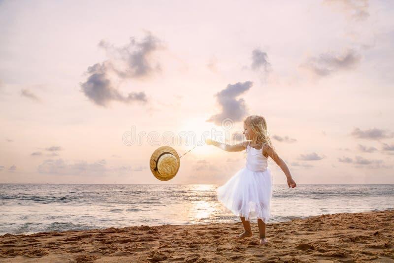 Gullig litet barnflicka med blont hår i en vit ballerinakjolklänning och hatt som går på en sandig strand på solnedgången lycklig royaltyfri fotografi