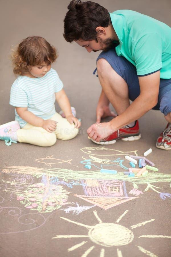 Gullig litet barnflicka och hennes faderteckning med färgkrita royaltyfri foto