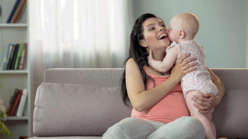 Gullig litet barnflicka som kysser och kramar hennes moder, förälskelse och mjukhet i familj royaltyfri foto