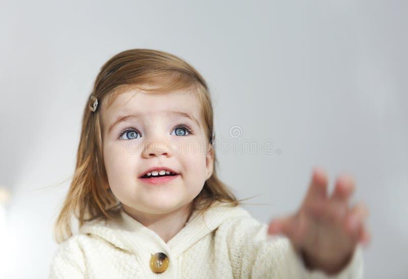 gullig litet barnflicka som ser bort isolerad p? vit arkivbild