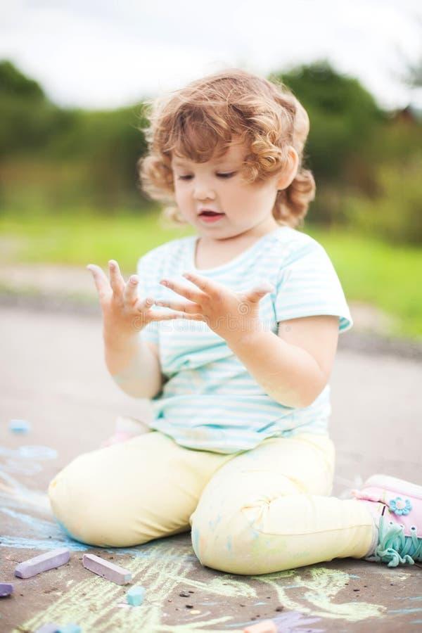 Gullig litet barnflicka som ser hennes smutsiga händer royaltyfria foton